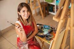 享受工作的华美的女性艺术家 免版税库存照片