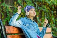 享受强有力的声音 感到令人敬畏 凉快的质朴的女孩享受在室外的耳机的音乐 女孩在公园听音乐 库存照片