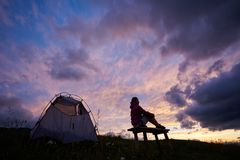 享受惊人的日落的年轻女性游人在山的帐篷附近在罗马尼亚 库存图片