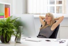 享受成功的天的妇女在工作 免版税库存图片