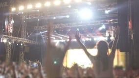 享受摇滚乐队表现,跳舞和唱歌在展示的爱好者人群  股票录像