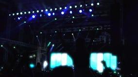 享受摇滚乐音乐会,挥动手和跳舞的激动的观众剪影 股票录像