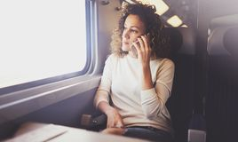 享受旅行概念 旅行乘火车的年轻俏丽的妇女游人坐在窗口附近使用智能手机 免版税图库摄影