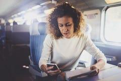 享受旅行概念 旅行乘火车的年轻俏丽的妇女游人坐在窗口附近使用智能手机 图库摄影
