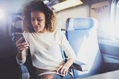 享受旅行概念 旅行乘火车的年轻俏丽的妇女游人坐在窗口附近使用智能手机 库存图片