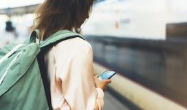 享受旅行 等待在有背包的驻地平台的年轻俏丽的妇女在背景电车使用智能手机 免版税库存图片