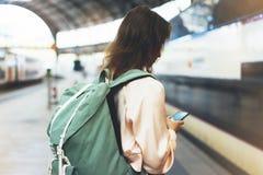 享受旅行 等待在有背包的驻地平台的年轻俏丽的妇女在背景电车使用智能手机 免版税库存照片