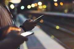 享受旅行 等待在背景光电移动的火车的驻地平台的少妇使用巧妙的电话在夜 免版税库存照片
