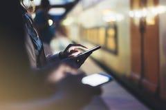 享受旅行 等待在背景光电移动的火车的驻地平台的少妇使用巧妙的电话在夜 免版税图库摄影