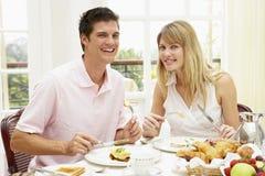 享受旅馆中间名的变老的早餐夫妇 免版税图库摄影