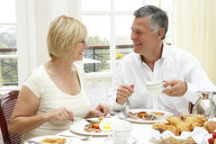享受旅馆中间名的变老的早餐夫妇 免版税库存照片