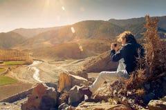 享受日落和拍照片的年轻远足者 免版税图库摄影
