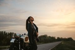 享受日落的女孩,当支持摩托车时 免版税库存图片