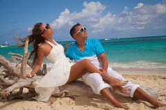 享受日落的愉快的浪漫夫妇在海滩 免版税库存照片