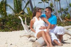 享受日落的愉快的浪漫夫妇在海滩 免版税库存图片