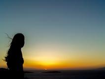 享受日落的游人在风车在米科诺斯岛 免版税库存图片