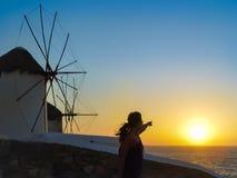 享受日落的游人在风车在米科诺斯岛 库存照片
