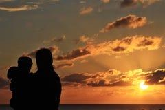 享受日落的父亲和女儿 免版税库存照片