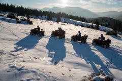 享受日落,在越野四轮汽车ATV的人在山的雪骑自行车在冬天 免版税库存照片