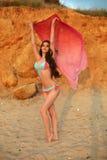 享受日落 比基尼泳装的美丽的少妇在海滩, 免版税库存照片