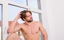 享受早晨受欢迎的新的令人敬畏的天 强壮男子的性感的人松弛近的窗口卧室 强壮男子放松在早晨卧室 免版税库存照片
