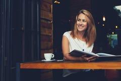 享受早晨好的愉快的微笑的行家女孩,当放松在舒适咖啡馆酒吧在工作天以后时 库存图片