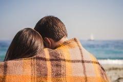 享受时间的年轻愉快的爱恋的夫妇在坐和拥抱在海洋,愉快的生活方式家庭观念附近的海滩 库存照片