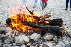 享受时间的家庭由河和自制营火 库存图片