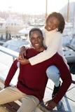 享受时间的愉快的黑夫妇一起花费,当坐在巴塞罗那时游艇港  免版税库存照片
