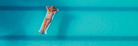 享受晒黑 美丽的概念池假期妇女年轻人 亭亭玉立的少妇顶视图比基尼泳装的在大游泳池横幅的蓝天床垫 免版税库存照片