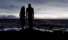 享受晚上的夫妇在海滩边 免版税图库摄影