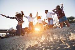 享受暑假的小组愉快的青年人 免版税库存图片