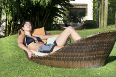 享受暑假的愉快的妇女说谎在一个热带庭院里sunbed 库存照片