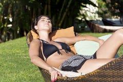 享受暑假的愉快的妇女说谎在一个热带庭院里sunbed 库存图片