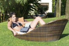 享受暑假的愉快的妇女说谎在一个热带庭院里sunbed 图库摄影