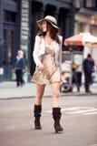 享受步行和穿过纽约街道的美丽的愉快的妇女 免版税库存图片