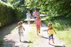享受步行的亚洲家庭在乡下 图库摄影