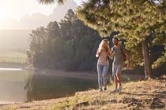 享受步行的夫妇由远足冒险的家庭的湖 库存照片