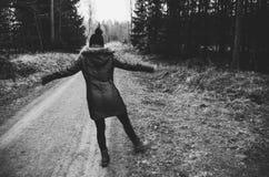 享受步行的妇女在黑白的森林里- 免版税图库摄影