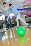 享受比赛十别针保龄球的两个年轻人 库存图片