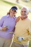 享受比赛高尔夫球的夫妇 免版税库存照片