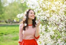 享受气味开花的春天的美丽的微笑的少妇 免版税库存图片