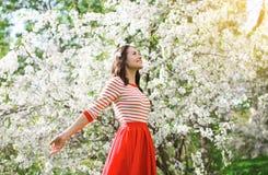 享受气味开花的春天的美丽的愉快的少妇 免版税库存照片