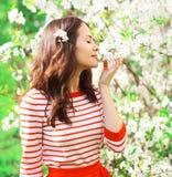 享受气味春天的美丽的少妇在庭院里开花 免版税库存图片