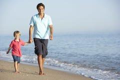 享受沿海滩的父亲和儿子步行 免版税库存图片