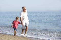 享受沿海滩的祖父和孙子步行 免版税库存照片