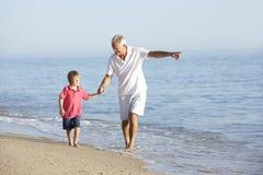 享受沿海滩的祖父和孙子步行 库存图片