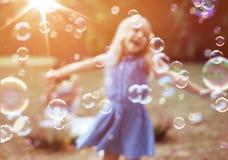 享受泡影吹的快乐的女孩 库存图片