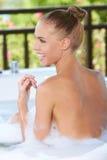 享受泡末浴的愉快的妇女 免版税库存图片