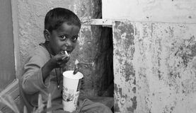 享受泡沫腾涌的饮料的街道男孩 库存图片